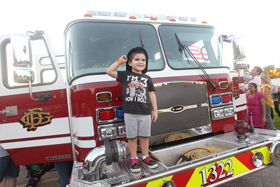 Candace H. Johnson-For Shaw Media Dominic Cocom, 3, of Waukegan holds on to his junior firefighters hat as he stands on a Gurnee Fire Department fire truck during the Gurnee Park District's 10th Annual Touch-A-Truck at the Hunt Club Park Community Center in Gurnee. (9/13/19)
