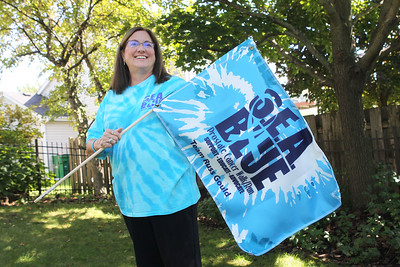 Candace H. Johnson-For Shaw Media Nancy Gould-O'Brien, helping to raise education and awareness about prostate cancer, holds a flag used during the annual SEA Blue Prostate Cancer5K Run/Walk on September 15th in Chicago, at her home in Grayslake. The event was founded by her father, Russ Gould, who passed away from the disease five years ago. (9/16/19)