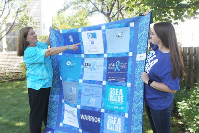 Candace H. Johnson-For Shaw Media Nancy Gould-O'Brien talks to her daughter, Shannon, 23, about the quilt of t-shirts made in honor of her father, Russ Gould, who was founder of an event called the SEA Blue Prostate Cancer 5K Run/Walk, at their home in Grayslake.The annual walk took place in Chicago on September 15th.  (9/16/19)