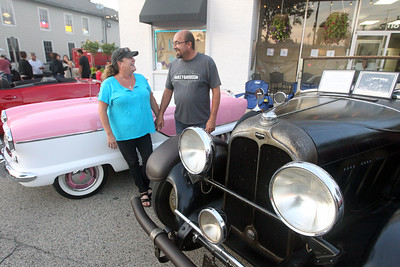 Candace H. Johnson-For Shaw Media Tracy and Chuck McCarthy, of Wauconda hold hands as they stand next to their cars, a 1959 Nash Metropolitan Convertible and a 1930 Auburn 8-95 Phaeton-Sedan during Wauconda Cruise Night on Main Street in Wauconda. (9/17/19)