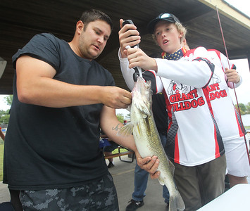 Candace H. Johnson-For Shaw Media Josh Norwick, of Fox Lake gets the walleye weighed that he caught with his son, Josh, 3, by Rick Hamann, 17, of Fox Lake during the 3rd Annual Fox Lake Fish Fest Youth Fishing Derby at Lakefront Park in Fox Lake. The walleye weighed in at 4 lbs. 8 oz. (9/20/19)