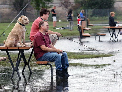 Candace H. Johnson-For Shaw Media Logan Johnson, 14, of Ingleside fishes with his father, Robert, and dog, Cooper, as they stay dry fishing off of a picnic bench in flooded water during the 3rd Annual Fox Lake Fish Fest Youth Fishing Derby at Lakefront Park in Fox Lake. (9/20/19)