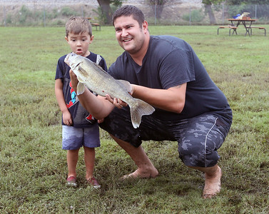 Candace H. Johnson-For Shaw Media Josh Norwick, 3, of Fox Lake reacts as he and his dad, Josh, get their photo taken with the 23-1/2 inch walleye they caught during the 3rd Annual Fox Lake Fish Fest Youth Fishing Derby at Lakefront Park in Fox Lake. (9/20/19)