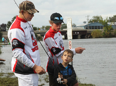 Candace H. Johnson-For Shaw Media Patryk Drag, 16, of Round Lake and Rick Hamann, 17, teach Nate Gilani, 6, both of Fox Lake how to fish during the 3rd Annual Fox Lake Fish Fest Youth Fishing Derby at Lakefront Park in Fox Lake. (9/20/19)