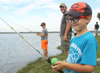 Candace H. Johnson-For Shaw Media Kyle Waggoner, of Lakemoor (center) fishes with his sons, Jake, 9, and Cole, 5, during the 3rd Annual Fox Lake Fish Fest Youth Fishing Derby at Lakefront Park in Fox Lake. (9/20/19)