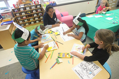 Candace H. Johnson-For Shaw Media Kalpana Boyina, of Waukegan (center) volunteers to help children color including her daughter, Anandi, 5, (on her right) in Miss Dalessandro's kindergarten class during the Green Apple Day of Service at Woodland Primary School in Gurnee. (9/20/19)