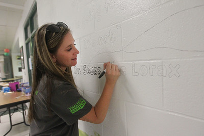 Candace H. Johnson-For Shaw Media Stacey Bloom, of Kenosha, Wis., interventionist, works on a mural as she outlines a quote from Dr. Seuss during the Green Apple Day of Service at Woodland Primary School in Gurnee. (9/20/19)
