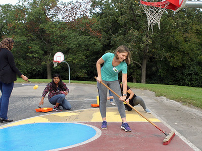 Candace H. Johnson-For Shaw Media Steph Dvorak, of Grayslake sweeps the basketball court as other volunteers paint a section of it during the Green Apple Day of Service at Woodland Primary School in Gurnee. (9/20/19)
