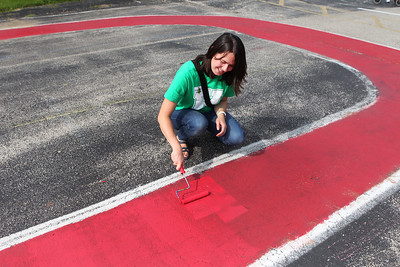 Candace H. Johnson-For Shaw Media Volunteer Claire Plowgian, of Gurnee helps to paint a tricycle race track outside in the Peaceful Playground during the Green Apple Day of Service at Woodland Primary School in Gurnee. (9/20/19)