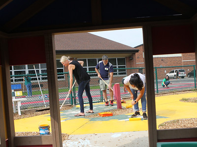 Candace H. Johnson-For Shaw Media Hannah Gross, Mike Shrear, both of Gurnee and Jessica Luna, of Park City paint a tricycle race track during the Green Apple Day of Service at Woodland Primary School in Gurnee. (9/20/19)