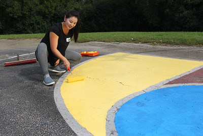 Candace H. Johnson-For Shaw Media Volunteer Elise Park, of Gurnee paints a section of the basketball court during the Green Apple Day of Service at Woodland Primary School in Gurnee. Park's son, Vincent Meyers, 5, goes to the school. (9/20/19)