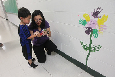 Candace H. Johnson-For Shaw Media Nicolas Guzman, 3, of Grayslake gets some help from his mother, Gloria, dipping his thumb in red paint to  use his thumbprint to make a lady bug on the wall on one of the hallways during the Green Apple Day of Service at Woodland Primary School in Gurnee. (9/20/19)