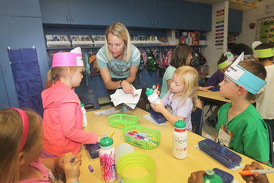 Candace H. Johnson-For Shaw Media Volunteer Kristine Pikula, of Gurnee talks to children about their pledge not to use disposable water bottles as they decorate reusable water bottles in Mrs. Julie Mayfield's kindergarten class during the Green Apple Day of Service at Woodland Primary School in Gurnee. Pikula has a daughter, Mackenzi, 5, who attends the school. (9/20/19)