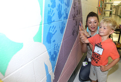 Candace H. Johnson-For Shaw Media Sarah Baier, of Woodstock, music teacher, helps Anthony Nustro, 5, put his hand print on the wall for a large mural in the hallway during the Green Apple Day of Service at Woodland Primary School in Gurnee. (9/20/19)