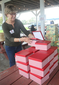Candace H. Johnson-For Shaw Media Volunteer Barb Ferguson, of Deerfield arranges sidewalk sale items including red stacking boxes in the Community Tent Sale during Fall on the Farm at Lambs Farm in Libertyville. (9/21/19)