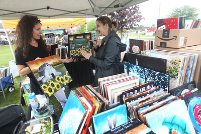 Candace H. Johnson-For Shaw Media Michele Muzones, owner, and Pat Gipple, event manager, both of Lindenhurst with Art Rave Inc., a wine and paint company, talk about the paintings they had for sale in the Community Tent Sale during Fall on the Farm at Lambs Farm in Libertyville. (9/21/19)