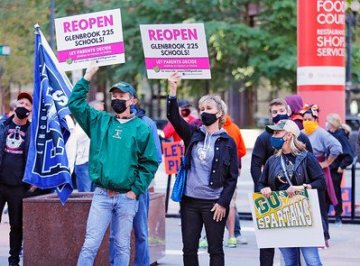"""Demonstrators listen to speakers at the """"Let Us Play"""" rally in support of a return to high school sports on Saturday, September 19, 2020 at the James R. Thompson Center in Chicago, IL."""