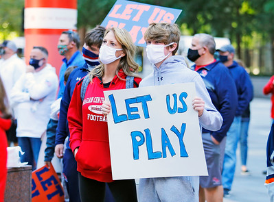 """Amy Hernon (left) and her son Brendon, a student at Marian Central high school, listen to speakers gathered at the """"Let Us Play"""" rally in support of a return to high school sports on Saturday, September 19, 2020 at the James R. Thompson Center in Chicago, IL."""