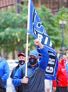 """A demonstrator displays a Lincoln Way East high school flag at the """"Let Us Play"""" rally in support of a return to high school sports on Saturday, September 19, 2020 at the James R. Thompson Center in Chicago, IL."""