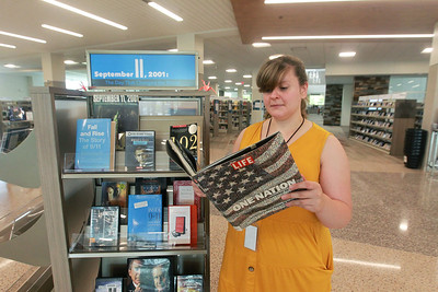 Candace H. Johnson-For Shaw Media Annie Tillmann, of Park Ridge, adult services program specialist, looks at one of the 9/11 books on display to commemorate the 20th Anniversary of 9/11 at the Lake Villa District Library in Lindenhurst.  (9/7/21)
