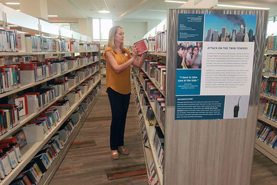 Candace H. Johnson-For Shaw Media Nami Quaranta, of Lindenhurst, learning & development coodinator, puts away an audiobook close to a 9/11 poster on display to commemorate the 20th Anniversary of 9/11 at the Lake Villa District Library in Lindenhurst. Fourteen 9/11 posters are on display which came from the 9/11 National Memorial & Museum  in New York. (9/7/21)