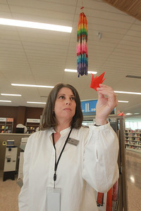 Candace H. Johnson-For Shaw Media Tara Caldara, of Beach Park, head of adult services, holds a paper crane with a paper crane chain hanging behind her on display to commemorate the 20th Anniversary of 9/11 at the Lake Villa District Library in Lindenhurst. She lent the library the paper crane chain, made of 1000 paper cranes, which was made by her pen pal from Tokyo and sent to her after 9/11. Cranes are symbols of hope and resilience.  (9/7/21)
