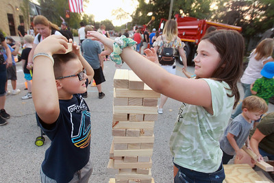 Candace H. Johnson-for Shaw Media Toby Schultz, 7, of Round Lake Beach and his sister, Ally, 10, play Jenga during the Celebration of Fall event on Cedar Avenue in Lake Villa.  (9/11/21)