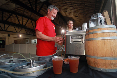 Candace H. Johnson-for Shaw Media Joe Van Heirseele, of Gurnee, owner, and Izzy Stilson, of Winthrop Harbor, bartender, both with the Harbor Brewing Co., serve craft beer in their new location under construction during the Celebration of Fall event on Cedar Avenue in Lake Villa.  (9/11/21)