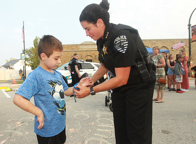 Candace H. Johnson-for Shaw Media Konner Marienthal, 7, of Lake Villa gets a pair of handcuffs taken off by Rochelle Tisinai, Lake Villa police chief, in the control tactics obstacle course during the Celebration of Fall event on Cedar Avenue in Lake Villa.  (9/11/21)