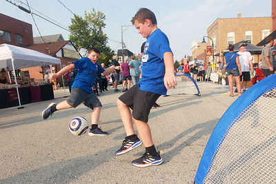 Candace H. Johnson-for Shaw Media Jackson Hejazinia, of Lindenhurst and his brother, Mason, twin brothers, 10, have fun playing soccer during the Celebration of Fall event on Cedar Avenue in Lake Villa. The brothers play soccer with the Lindenhurst Area Soccer Club.  (9/11/21)