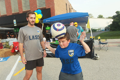 Candace H. Johnson-for Shaw Media Ryan Kelekian, a coach with the Lindenhurst Area Soccer Club, teaches Jackson Hejazinia, 10, both of Lindenhurst how to properly head the ball in soccer during the Celebration of Fall event on Cedar Avenue in Lake Villa.  (9/11/21)