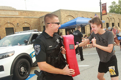 Candace H. Johnson-for Shaw Media Austin Demski, Lake Villa police officer, holds a striking bag for Alexander Cromack, 15, of Round Lake Beach to punch in the control tactics obstacle course during the Celebration of Fall event on Cedar Avenue in Lake Villa.  (9/11/21)