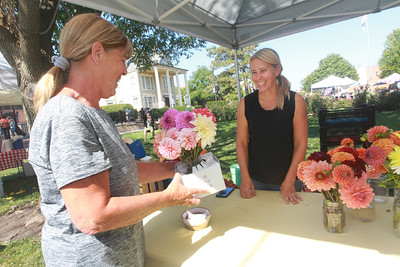 Candace H. Johnson-for Shaw Media Tania Cubberly, flower farmer and owner of Skyfall Flowers, (on right) sells a bouquet of Dahlias she grows on her farm within the Prairie Crossing Farm to Peggy Meo, of Mundelein at the Libertyville Farmers Market. Cubberly sells her Dahlias at the Libertyville Farmers Market on Thursdays 7am to 1pm through October 21st.  (9/17/21)