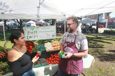 Candace H. Johnson-for Shaw Media Eric Carlberg, of Kenosha, Wis., (on right) program manager with the Prairie Farm Corps Liberty Prairie Foundation, talks to one of his former students, Laura Caballero, of Hainesville, as she visits him at the Libertyville Farms Market while he was selling organic vegetables from the Prairie Crossing Farm in Grayslake.  (9/17/21)