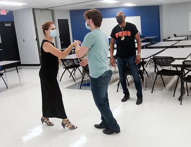 Candace H. Johnson-for Shaw Media Pam Yadanza, of Lake Villa and her son, Zach, 22, practice basic dance steps as they take direction from Richard Hill, instructor, during the Latin Social Dance Class at the College of Lake County in Grayslake.  Hill is the co-owner of the Dress Up & Dance! On the Move mobile dance organization. (9/27/21)