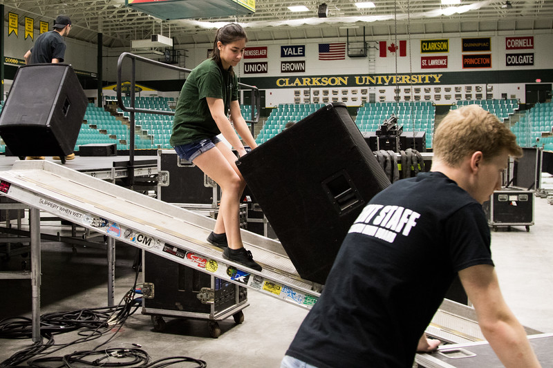 CUB members loading speakers onto the stage to be used as monitors for the musicians.