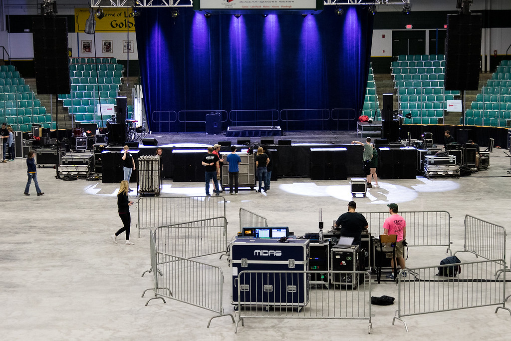 Overview photo of the arena showing the stage lighting is on and the front house audio is being set up.