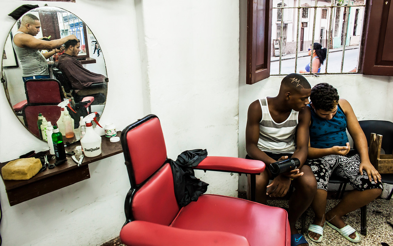 HAVANA - Two boys hang out at the barbershop after a fresh cut. In Havana, where resources are limited, style is less about clothing and expressed more through hair, making the barbershop is an integral part of life in Cuba.