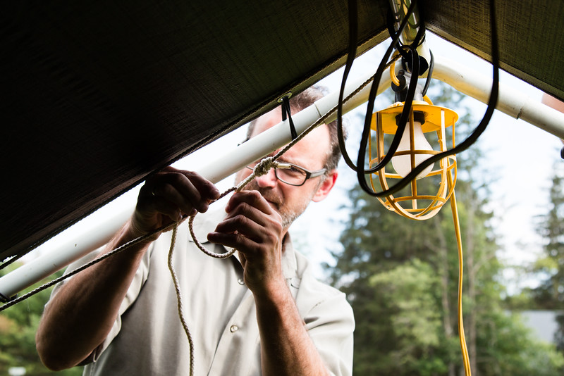John Olszewski, Assistant Scout Master tying lights to the top of the tent.