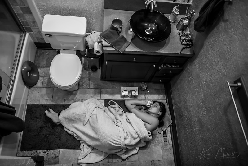 """DENVER - Less than a week after celebrating a successful vaginal birth at home, Lindsey can't escape the """"baby blues"""" and lies on the floor of her bathroom weeping.  The baby blues is not to be confused with postpartum depression, however it is much more common.  Four out of five women experience the baby blues with symptoms like crying without apparent cause and shifts in mood.  The baby blues is attributed to fatigue and to a dramatic shift of hormones that had been stored in the placenta but exit the body at childbirth."""