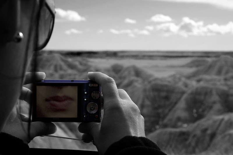 Badlands National Park ,South Dakota, USA Adjustment:  Black and white background. While Kate was taking a photo of the dramatic Badlands landscape I saw her lips reflecting in the screen of her camera.  I think it makes for a cool effect
