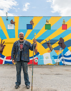 KCAD alumnus Ricardo Gonzalez ('16, MFA Painting) in front of the mural.