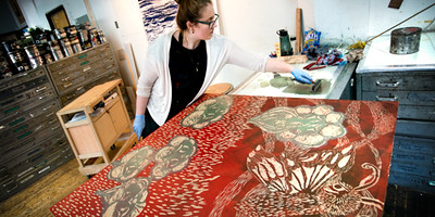 student applying ink to large woodcut