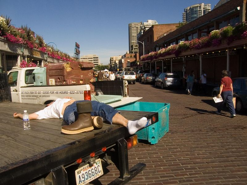 flower seller at Pike Place market takes a break after setting up his stall