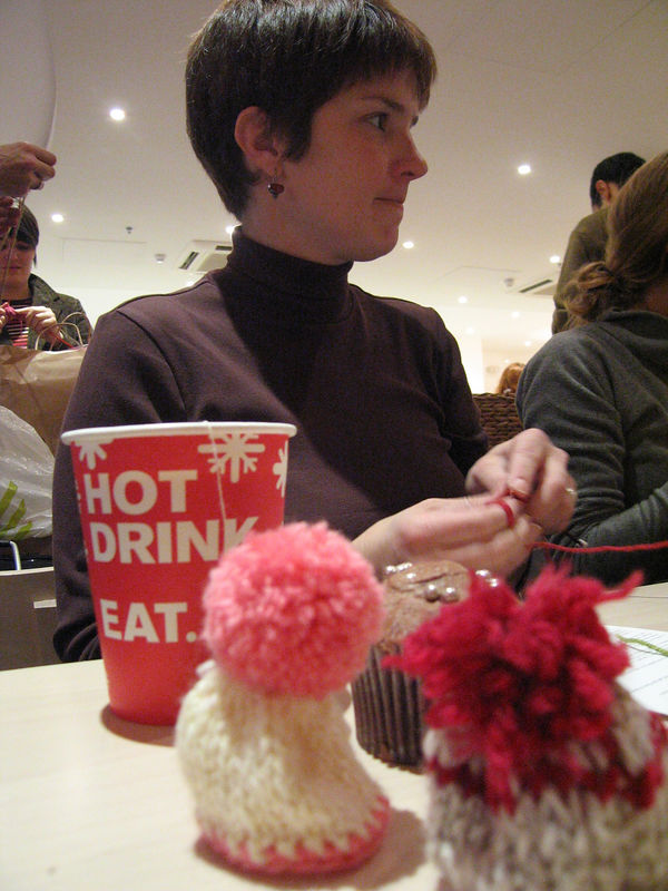 Leigh knitting little hats (for bottles of Innonence brand smoothies) to raise money for charity.  the EAT chain of restaurants is one of the sponsors of the fund-raising effort.