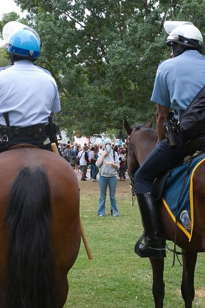 masked anti-war protester contemplates Park Police on horseback, Washington dc