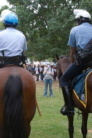 masked anti-war protester contemplates Park Police on horseback, Washington dc