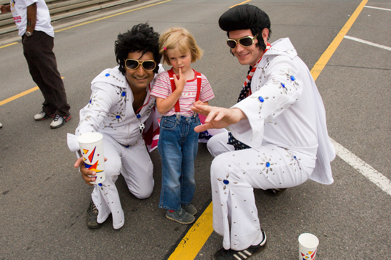 A child is forced to pose for her parents with the two Elvises.