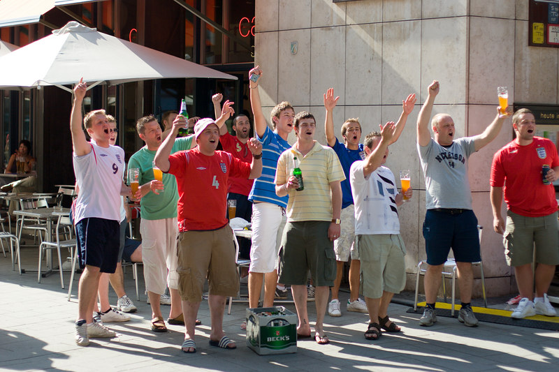 England fans drinking and singing patriotic songs at a nearby group of Germany fans in a square in Köln.
