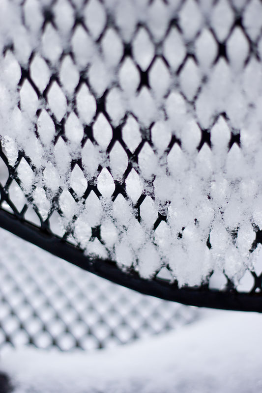 snow squeezing through the back of a patio chair on the roof deck of our building